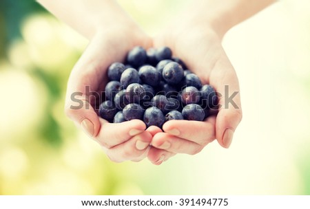 healthy eating, dieting, vegetarian food and people concept - close up of woman hands holding blueberries over green natural background