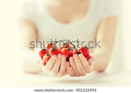 healthy eating, dieting, vegetarian food and people concept - close up of woman hands holding cherry tomatoes bunch at home - stock photo