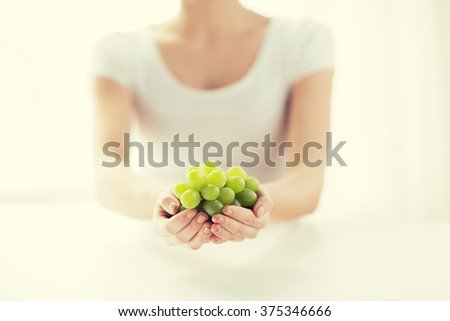healthy eating, dieting, vegetarian food and people concept - close up of woman hands holding green grape bunch at home - stock photo
