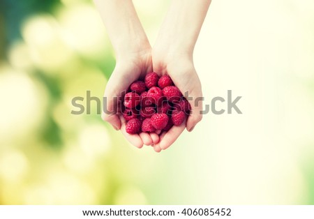 healthy eating, dieting, vegetarian food and people concept - close up of woman hands holding ripe raspberries over green natural background - stock photo