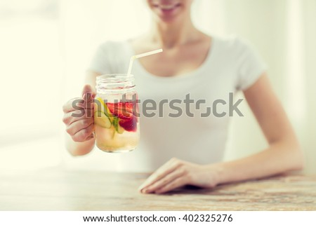 healthy eating, drinks, diet, detox and people concept - close up of happy woman holding glass with fruit water at home - stock photo