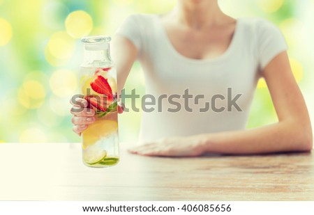 healthy eating, drinks, diet, detox and people concept - close up of woman with fruit water in glass bottle over green lights background - stock photo