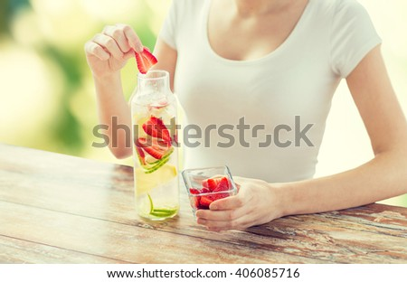 healthy eating, drinks, diet, detox and people concept - close up of woman with fruit water in glass bottle over green natural background - stock photo