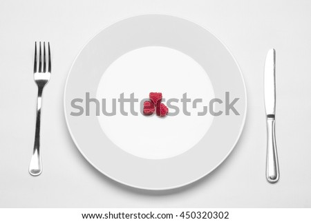 Healthy eating in the restaurant and diet Topic: white plate with three ripe raspberries and a metal knife and fork lying on a white table in the studio isolated top view