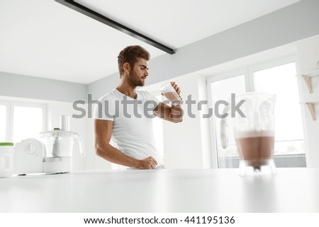 Healthy Eating. Muscular Man With Strong Muscles Drinking Protein Shake In Kitchen. Athletic Beautiful Sexy Fitness Male Model Enjoying Sports Drink Indoors. Bodybuilding Nutrition, Food Supplements - stock photo
