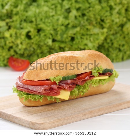 Healthy eating sub deli sandwich baguette with salami, cheese, tomatoes and lettuce