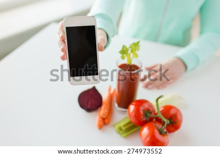 healthy eating, technology, diet and people concept - close up of woman hands with smartphone, tomato juice and vegetables - stock photo