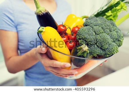 healthy eating, vegetarian food, diet and people concept - close up of woman holding vegetables in bowl - stock photo