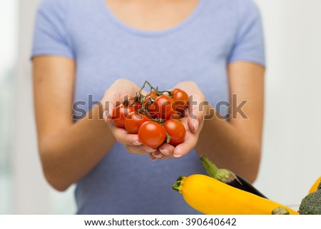 healthy eating, vegetarian food, diet , vegetables and people concept -close up of woman holding cherry tomatoes in hands