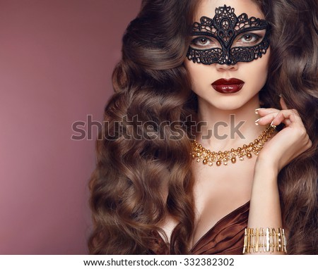Healthy elegant hairstyle. Beautiful brunette girl model. Fashion golden jewelry. Beauty glamour woman wearing in venetian masquerade carnival mask.