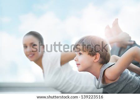 Healthy family - mother and son doing exercises against blue sky - stock photo