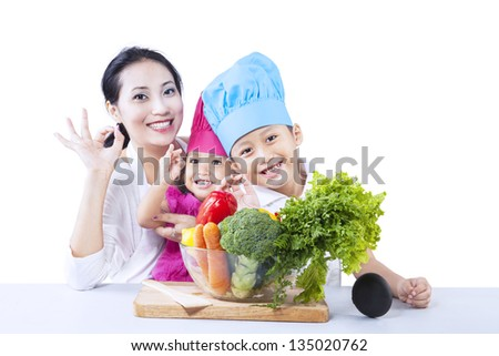 Healthy family with OK gesture and vegetable, isolated on white - stock photo