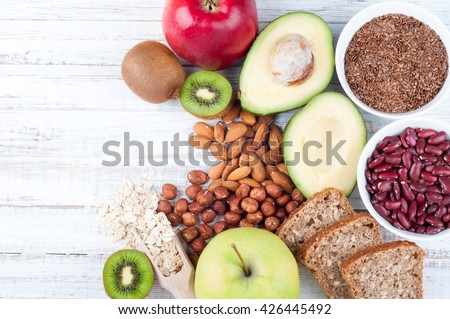 Healthy fat sources and healthy food that is useful for heart -  avocado, flax seeds, whole grain bread, nuts, beans, oatmeal and apples. Diet and healthy lifestyle concept. Vegetarian food. Top view - stock photo