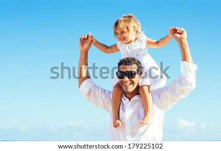 Healthy father and daughter playing together at the beach  - stock photo