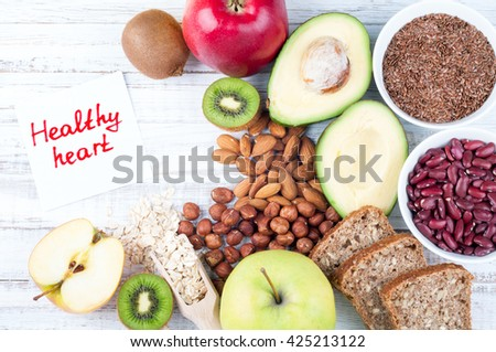 Healthy fats sources and healthy food that is useful for the heart on wooden background with note Healthy heart. Diet and healthy lifestyle concept. Top view - stock photo