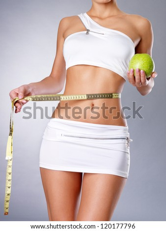 Healthy female body with apple and measuring tape. Healthy fitness and eating lifestyle concept. - stock photo