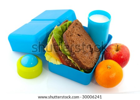 Healthy filled lunch box with whole meal bread vegetables and milk - stock photo