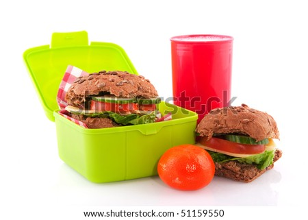 Healthy filled red lunchbox with brown bread rolls fruit and milk - stock photo