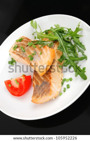 healthy fish cuisine  : baked pink salmon steaks garnished with tomatoes and rocula on white dish isolated over black background - stock photo