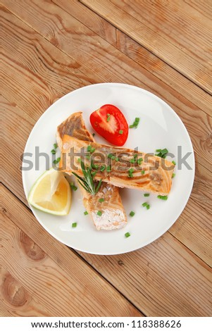 healthy fish cuisine  : grilled pink salmon steaks on white dish over wooden table