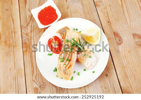 healthy fish cuisine  : grilled pink salmon steaks on white dish with red caviar over wooden table - stock photo