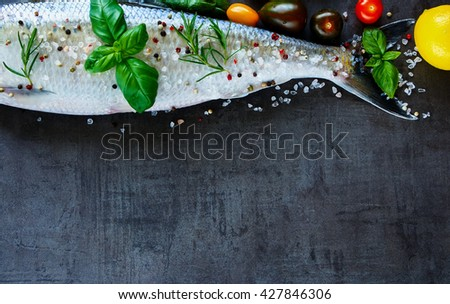 Healthy fish dishes cooking background with space for text. Raw fish with various ingredients on dark vintage board, preparation. Flat lay. Healthy food or diet nutrition concept. - stock photo