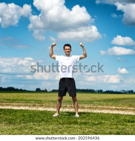 Healthy fit sportsman flexing his arms as he stands in an open rural field alongside a track in his sportswear smiling as he limbers up for his workout and training showing off his muscles - stock photo