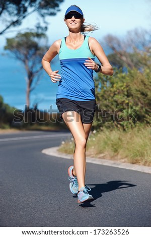 Healthy fit woman running on road for marathon exercise - stock photo