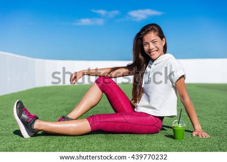 Healthy fitness Asian girl drinking green smoothie. Cute happy smiling woman relaxing during cardio training workout on outdoor grass gym enjoying vegetable juice morning breakfast in activewear. - stock photo