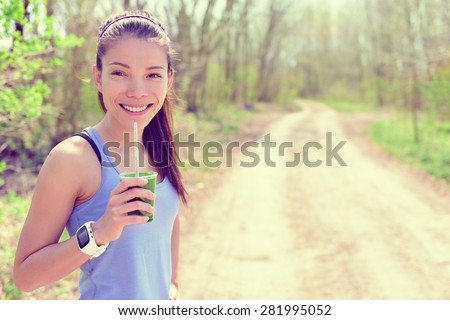 Healthy fitness girl drinking green spinach vegetable smoothie wearing smartwatch heart rate monitor during outdoor running workout in forest park during summer or spring. Happy fit Asian woman. - stock photo