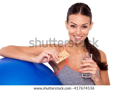 Healthy food after-workout is the way to success! Cropped shot of attractive sporty woman sitting next to her fitness ball and holding a protein bar with glass of water. - stock photo