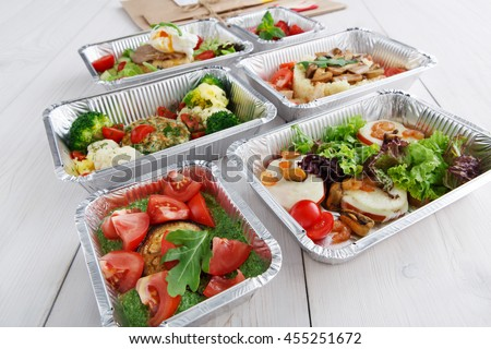Healthy food and diet concept. Take away of fitness meal. Weight loss nutrition in foil boxes. Vegetables, guacamole, mozarella cheese and other dishes closeup at white wood - stock photo