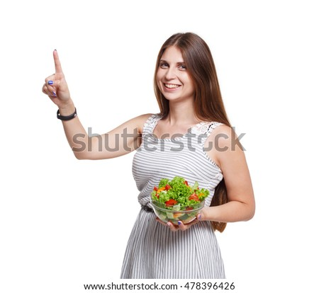 Healthy food and diet concept. Young smiling woman holds fresh vegetable salad meal and touch imaginary screen or push button isolated on white background. Modern dieting and weight loss nutrition