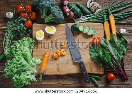 Healthy food and ingredients with tomato, arugula, carrots, beetroot, leaves, cucumber, onion, green, radish, mushrooms, garlic, broccoli, half, egg and peas on rustic wooden background, top view - stock photo