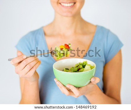 healthy food and kitchen concept - woman eating salad with vegetables