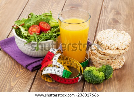 Healthy food and tape measure over wooden table. Fitness and health - stock photo