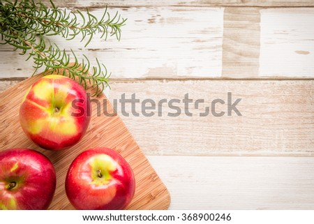 Healthy food arrangement with three red apples on a wooden board and rosemary leaves on a rustic wooden table. View from above/top. Copy space.