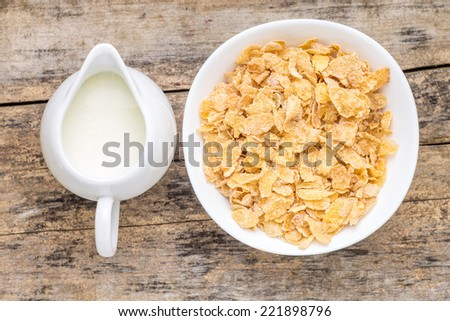 Healthy food background. Top view image of corn flakes and jar of milk - stock photo