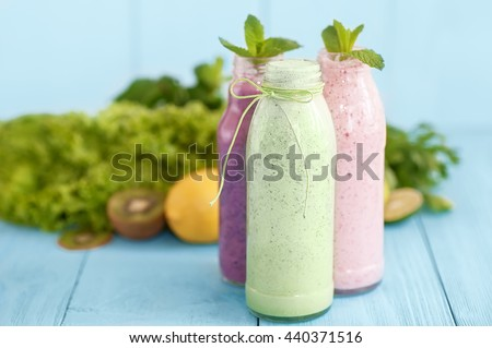 healthy food concept. milkshakes in glass and fresh green vegetables on natural blue wooden background - stock photo