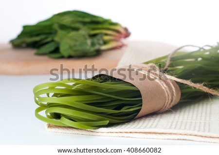Healthy food concept: uncooked spinach colorful raw italian pasta with spinach, over light background. Shot in shallow depth of field - stock photo