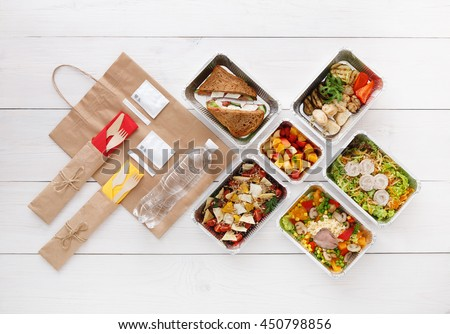 Healthy food delivery. Take away for diet. Fitness nutrition, vegetables, meat and fruits in foil boxes, cutlery, water and brown paper package. Top view, flat lay at white wood with copy space - stock photo