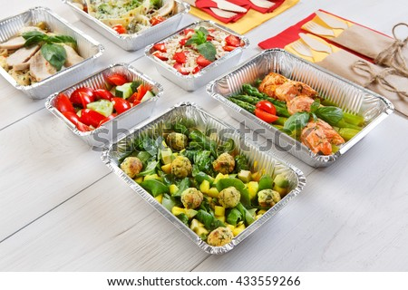 Healthy food delivery. Take away of natural organic low carb diet. Eat right concept, clean nutrition take away in foil boxes and bag, vegetables and salmon closeup