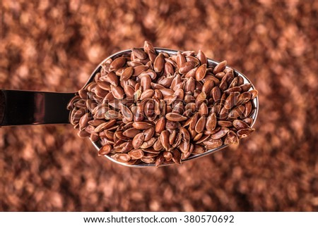 Healthy food diet. Closeup brown flax seeds linseed on kitchen spoon - stock photo