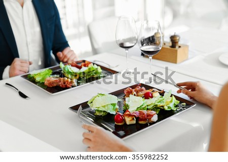 Healthy Food Eating. Closeup Of Young Couple Having Caesar Salad With Roast Chicken, Vegetables And Cheese For Meal In Luxury Gourmet Restaurant. People On Date. Romantic Dinner Or Lunch, Diet Concept - stock photo