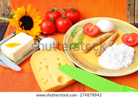 Healthy food for breakfast served on a bright color napkin with a sunflower - Cheese, butter, boiled eggs,cottage cheese, grain cookies, fresh tomatoes, salad leaves (rucola)and fresh tomatoes  - stock photo