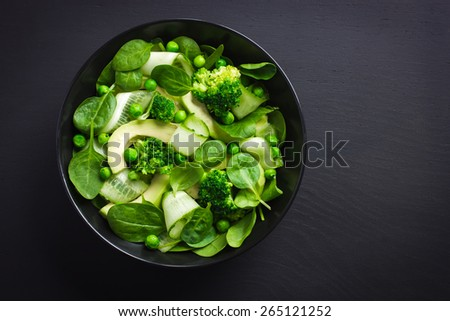 Healthy food. Fresh green salad on black background, top view - stock photo