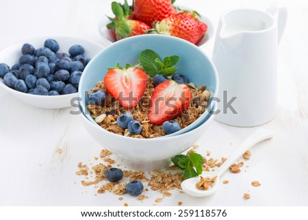 healthy food - granola, fresh berries and milk on white table, close-up, horizontal - stock photo