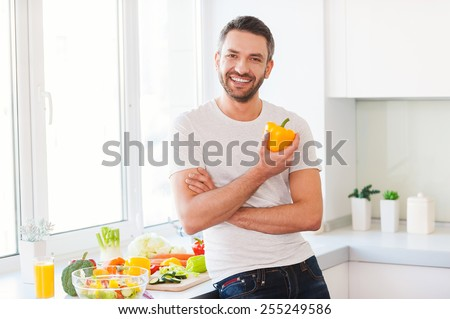 Healthy food is healthy life. Handsome young man holding fresh yellow pepper and smiling while standing in the kitchen  - stock photo