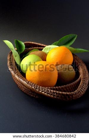 Healthy food. kiwi fruit, orange and apple insisde wicker basket - stock photo