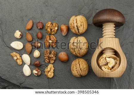 Healthy food - nuts. Walnut kernels and whole walnuts on slate. Walnuts and wooden nutcracker. We like walnuts. Advertising on walnuts. - stock photo